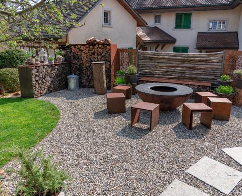 Gartenumänderung Einfamilienhaus, Sitzplatz mit Rundkies, Beläge mit Tessiner Gneis, Wasserbrunnen aus Granit