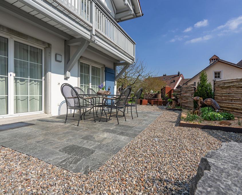 Gartenumänderung Einfamilienhaus, Sitzplatz mit Rundkies, Beläge mit Tessiner Gneis